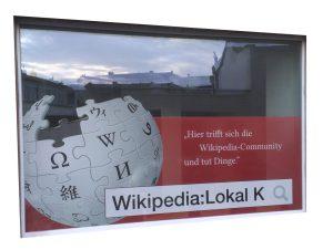 Das Schaufenster des Lokal K zeigt ein Puzzle in Form einer Weltkugel. Auf jedem Puzzle steht ein Buchstabe in unterschiedlichen Sprachen. Rechts daneben ist der Slogan des Lokals zu lesen.