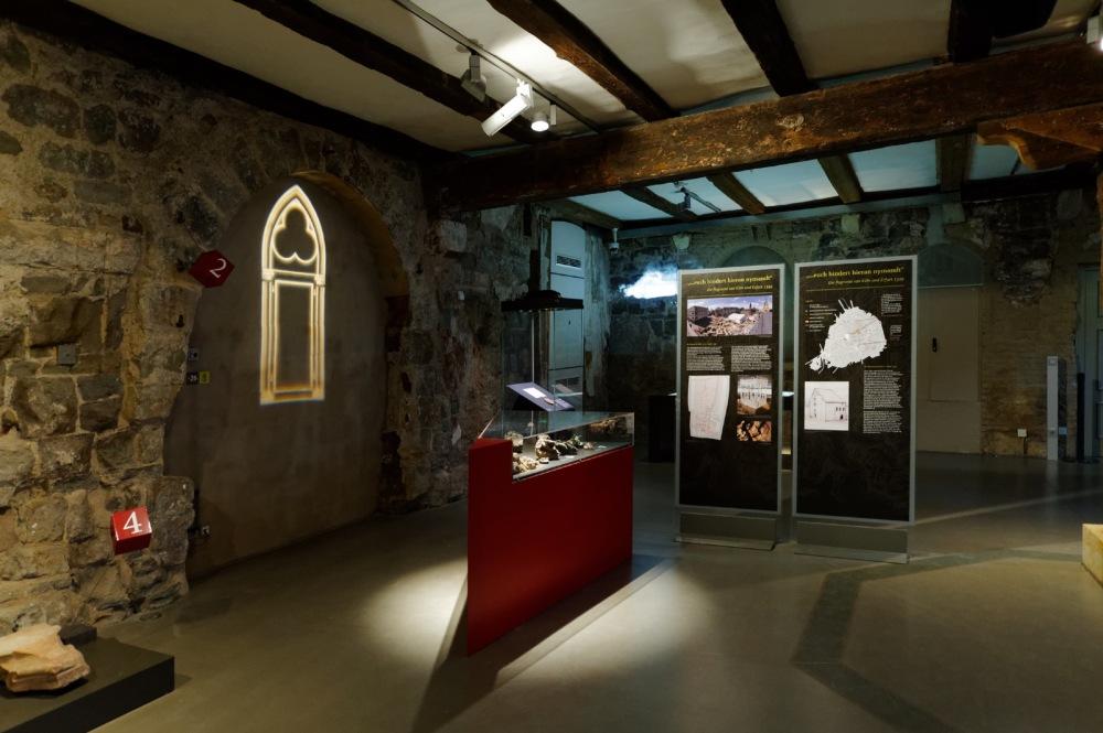 Ausstellungsraum mit zwei Stellwänden und einer Vitrine.