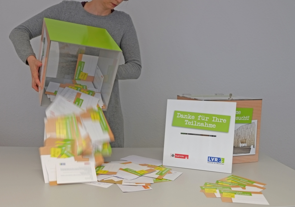 Eine Frau leert eine Box mit vielen Postkarten.