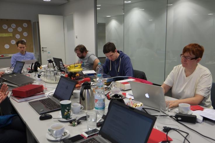 4 Personen arbeiten konzentriert an ihren Notebooks. Die Tischfläche wird voll genutzt - mit Technik und Kaffee.