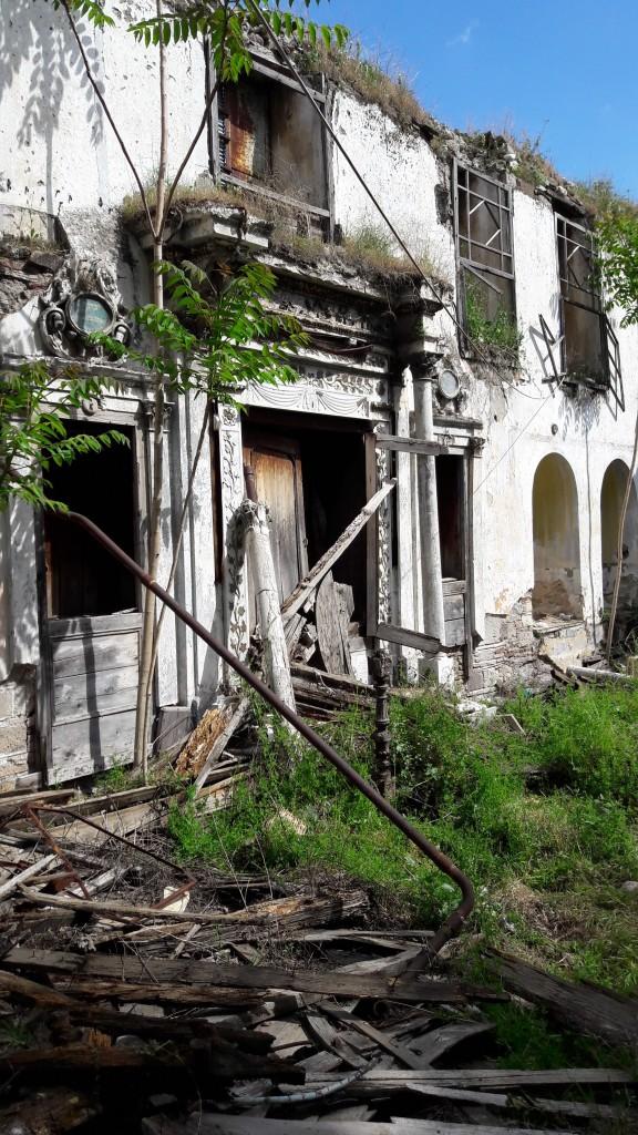 Die Synagoge ist stark zerstört und bewachsen. Im Vordergrund liegen Bretter.