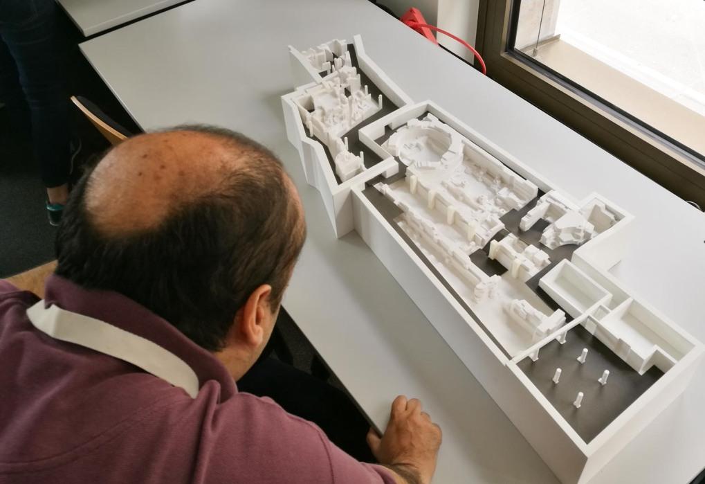 Ein Mann beugt sich über das 3D-Modell des Ausstellungsparcours.