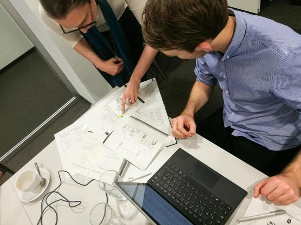 Eine Mitarbeiterin des MiQua zeigt einem Wikipedianer Pläne.