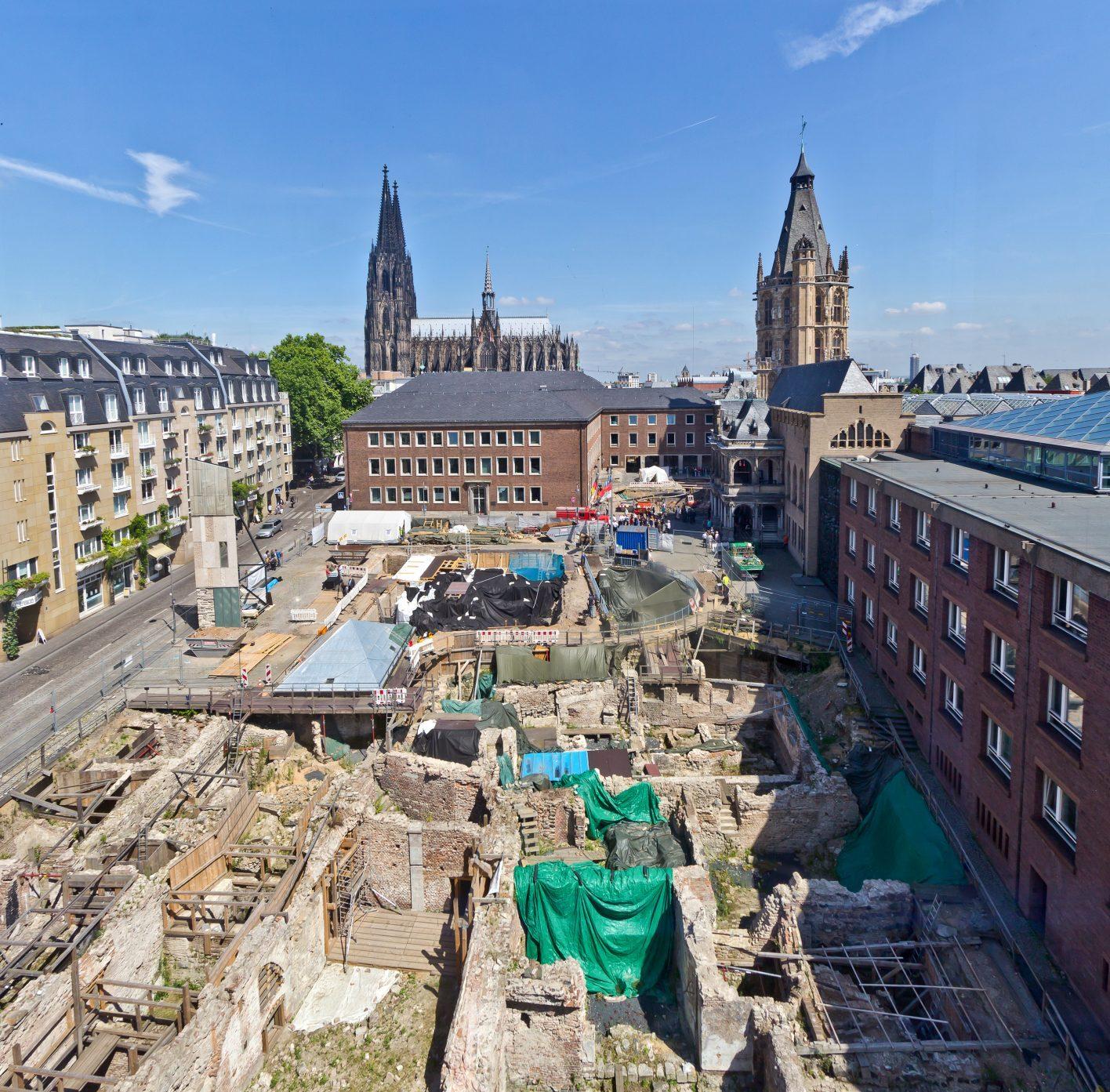 Die freigelegten Mauerreste des mittelalterlichen Viertels sind im Bildzentrum. Rechts ist das Historische Rathaus mit der Rathauslaube im oberen Bildbereich. Im Hintergrund ist der Kölner Dom zu sehen.