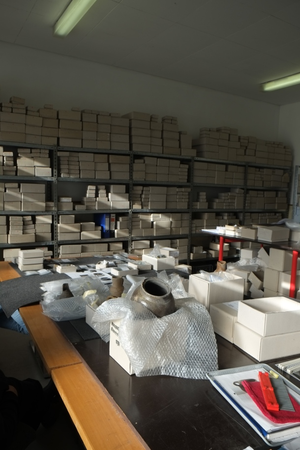 Auf einem großen Tisch stehen geschlossene und geöffnete Kisten, aus denen zum Teil Funde zu sehen sind. Im Hintergrund ein großes Regal mit Kartons unterschiedlicher Größen.