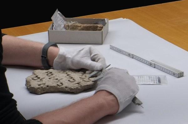 Detailaufnahme von zwei Händen in weißen Handschuhen, die einen Teil eines Fundes vermessen.