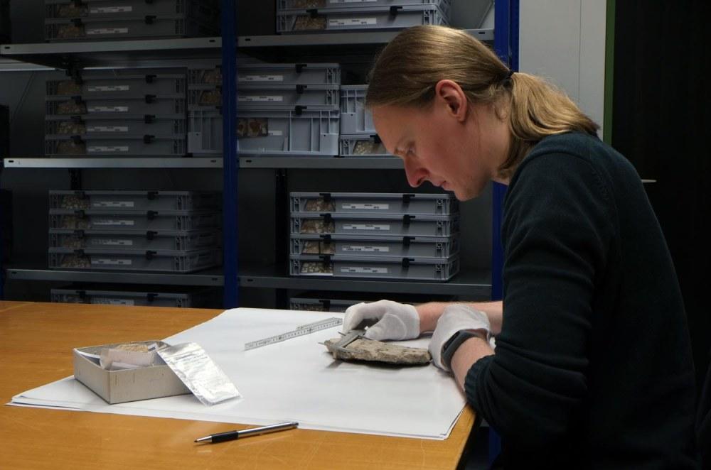 Seitliche Aufnahme eines Mitarbeiters, der einen Fund mit einem Messgerät untersucht.