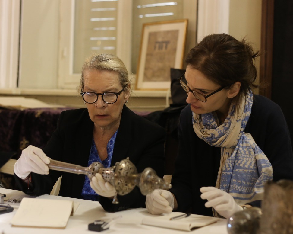 Zwei Frauen tragen weiße Handschuhe zum Schutz des Objektes. Frau Gogel hält das Objekt in beiden Händen.