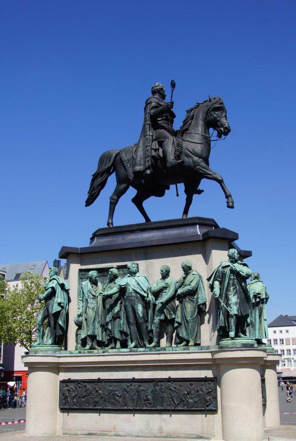 Ein Denkmal mit einem Sockel, auf dem verschiedene Personen stehend zu sehen sind. Darüber ein Reiter auf einem Pferd.