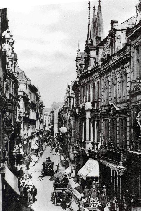 Historische schwarz-weiß Aufnahme mit Kutschen auf der Straße und den historischen Gebäuden. Rechts hinter den Häuserfassaden sind die Domspitzen zu sehen.
