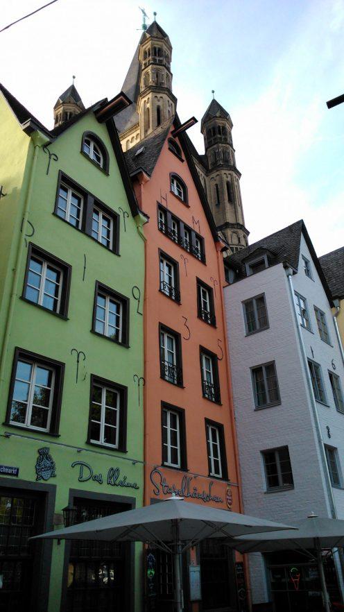 Drei bunt bemalte, schmale Häuser mit spitzen Dächern in der Kölner Altstadt.
