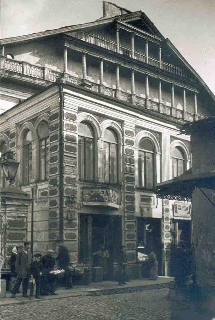 Schwarz-weiß Aufnahme des Gebäudes an einer belebten Straße.