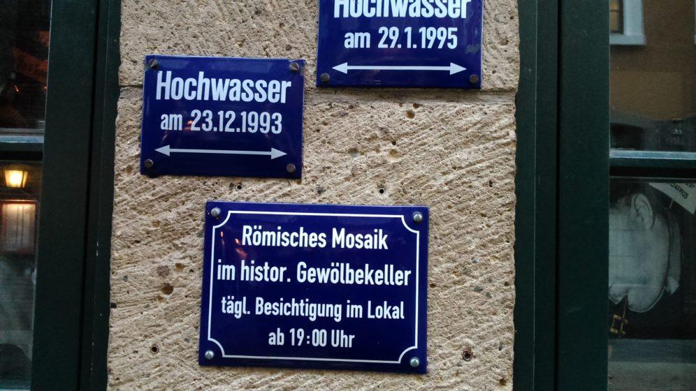 Auf dem Schild steht, dass das römische Mosaik täglich ab 19 Uhr im Lokal besichtigt werden kann. Weitere Schilder weisen auf das Hochwasser in den Jahren 1993 und 1995 hin.