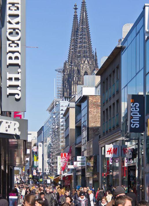 Foto der gut besuchten Einkaufsstraße mit Geschäftsschildern und rechts im Hintergrund die Spitzen des Kölner Doms.