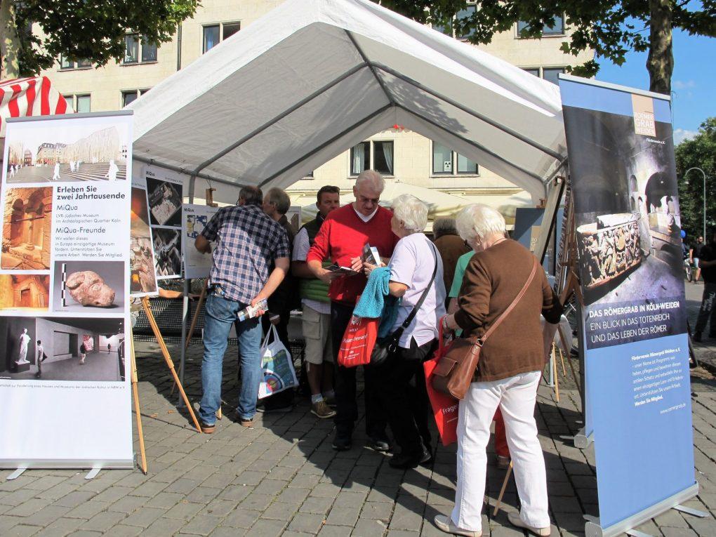 Mehrere Personen stehen im Zelt und unterhalten sich mit den Vereinsmitgliedern.