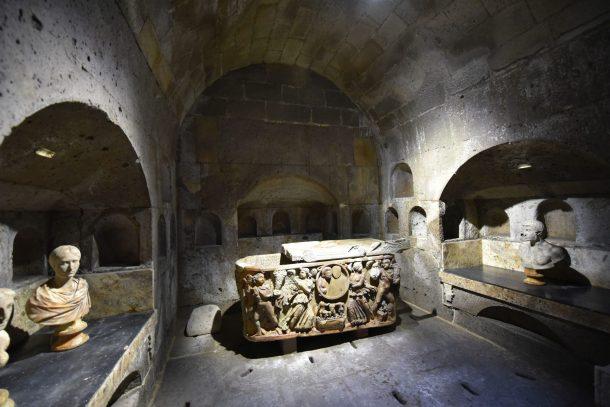 Gewölbe mit einem steinernen Sarkophag in der Bildmitte. Rechts und links römische Büsten.