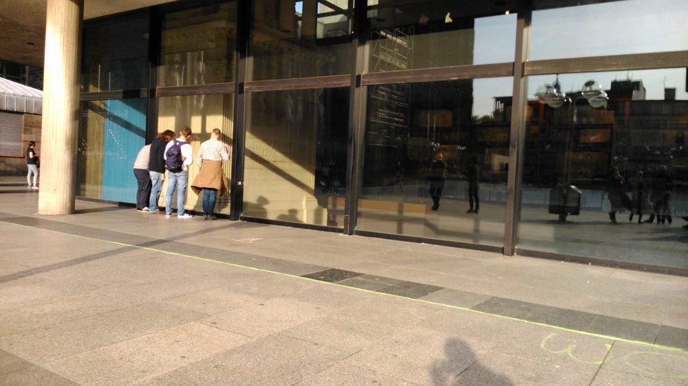 Vier Personen stehen dicht am Museumsfenster und schauen zum Mosaik herunter.