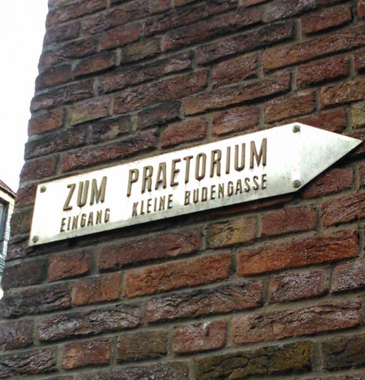 Hinweisschild zum Eingang Kleine Budengasse, angebracht an einer Hausfassade.