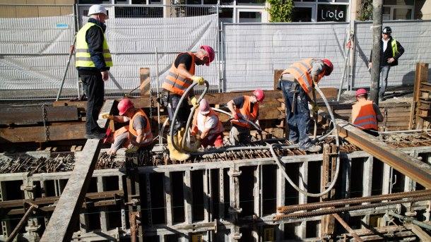 Mehrere Bauarbeiter beim Betonieren des Fundaments für das neue Museum