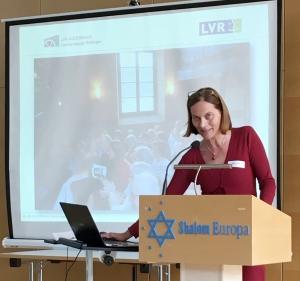 Frau Grübel steht am Rednerpult und spricht in eine Mikrofon. Im Hintergrund eine Leinwand mit einer Präsentation.
