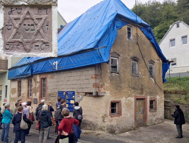 Besuchergruppe vor einem Gebäude. Am linken oberen Bildrand ist das Foto des Chuppa-Steins einmontiert.