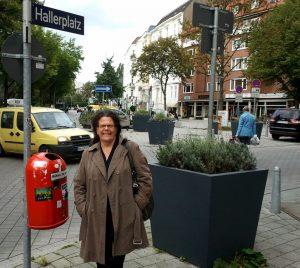 """Frontalaufnahme der lächelnden Annette Haller an einem Straßenschild mit der Aufschrift """"Hallerplatz""""."""