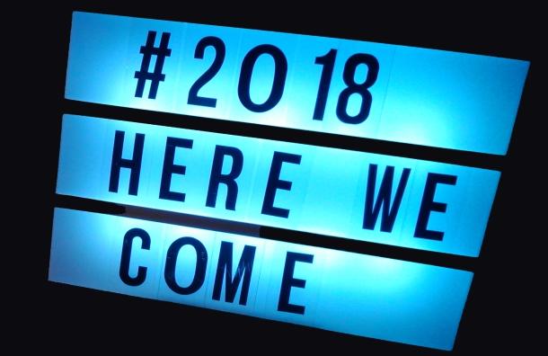 """Ein blau hinterleuchtetes Schild mit der Aufschrift """"2018 Here we come"""""""