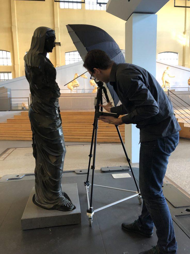Seitliche Ansicht der Statue. Vor ihr ist ein Fotostativ mit Schirm aufgebaut und eine Person, die das Stativ berührt.