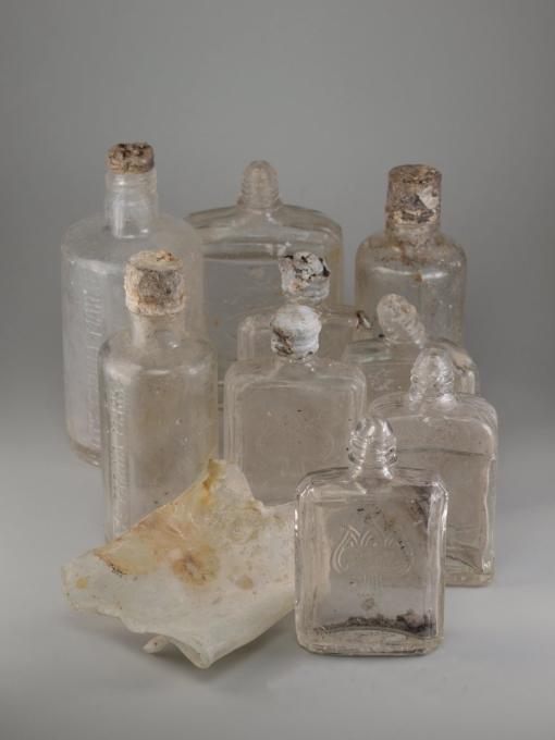 Fundobjekte aus der Grabung. Dabei handelt es sich um 9 Glasflaschen von Farina ohne Inhalt.