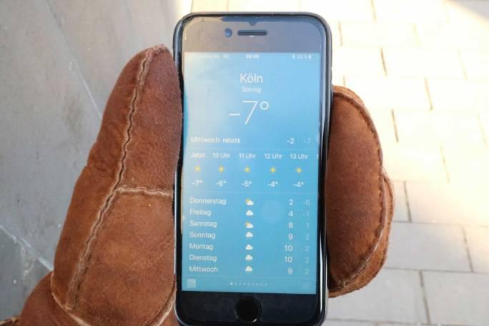 Smartphone in dicken braunen Handschuhen. Temperaturanzeige für Köln zeigt 7 Grad minus an.