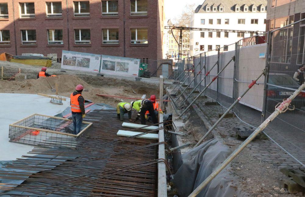 Drei Arbeiter montieren Stahlgeflecht auf der Baustelle des MiQua