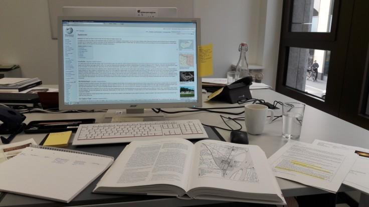 Arbeitsplatz mit Computer, Büchern und Notizen