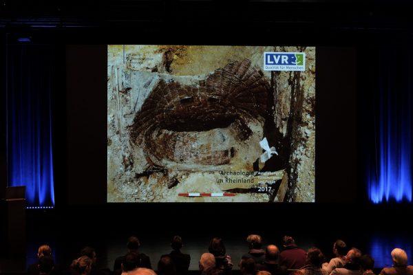 Frontalansicht einer großen Leinwand, auf der ein Ausgrabungsbild zu sehen ist. Im Vordergrund sitzendes Publikum.