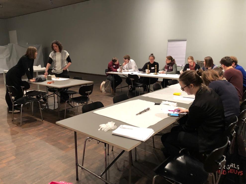 """Die Teilnehmer*innen des Workshops """"Objekte in jüdischen Sammlungen – Zufall oder Strategie"""" untersuchen gemeinsam Objekte aus der Sammlung des Jüdischen Museums München."""
