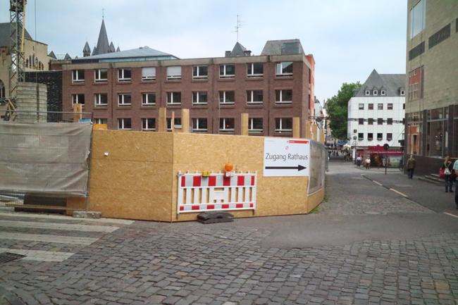 Der Bauzaun aus Holz um die MiQua-Baustelle. Rechts das Wallraf-Richartz-Museum
