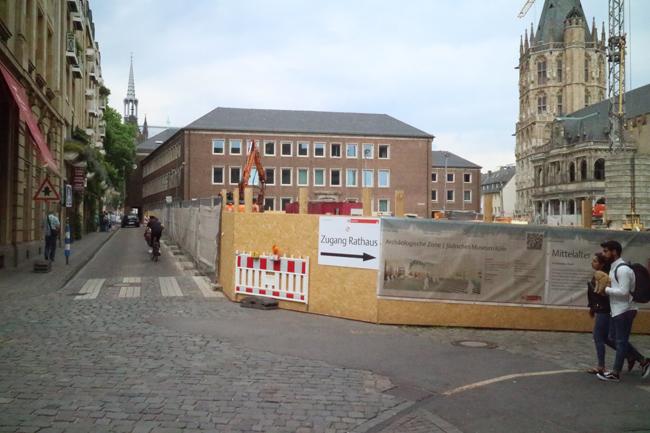 Der Bauzaun aus Holz um die MiQua-Baustelle. Rechts der historische Rathausturm und die Rathauslaube