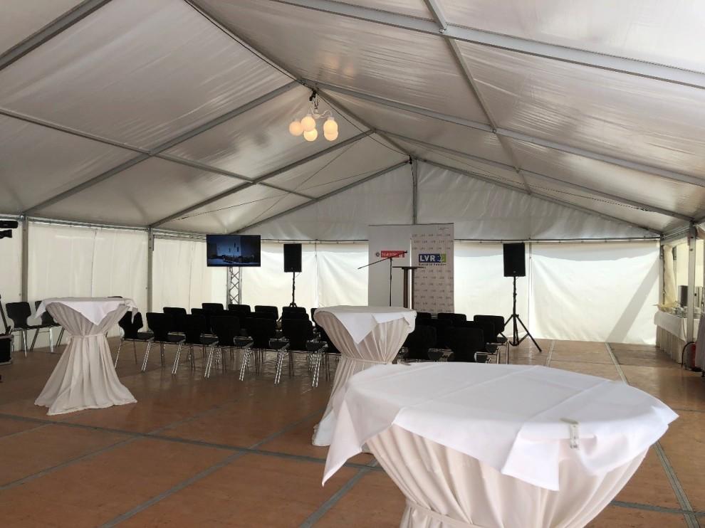 In einem Zelt wurden die Stuhlreihen aufgestellt. Das Podium ist an der Kopfseite des Zeltes aufgebaut. Im Vordergrund konnten die Gäste Platz an den Stehtischen finden.