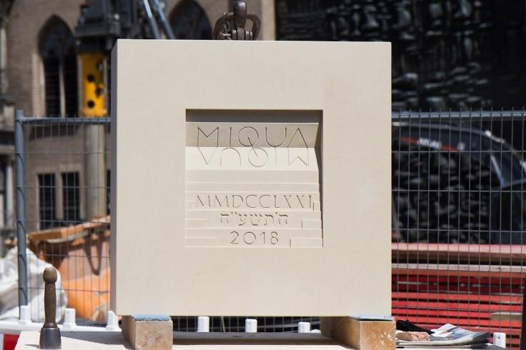 Der MIQUA-Grundstein aus Kalkstein in Form eines Quadrates. In der Mitte des Steins hervorgehoben der gespiegelte Schriftzug MIQUA sowie über Stufen dargestellt verschiedene Zeitrechnungen.