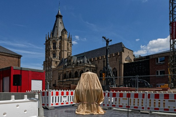 Im Hintergrund das Rathaus, davor die Baustelle mit dem verhüllten Grundstein.