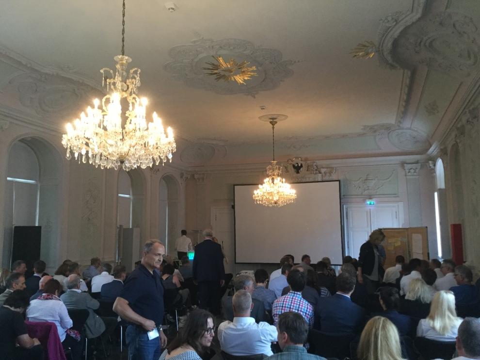 Ansicht des Tagungssaals mit den Teilnehmerinnen und Teilnehmern. Im Hintergrund eine Leinwand. Die Decke ist mit zwei Kronleuchtern verziert.