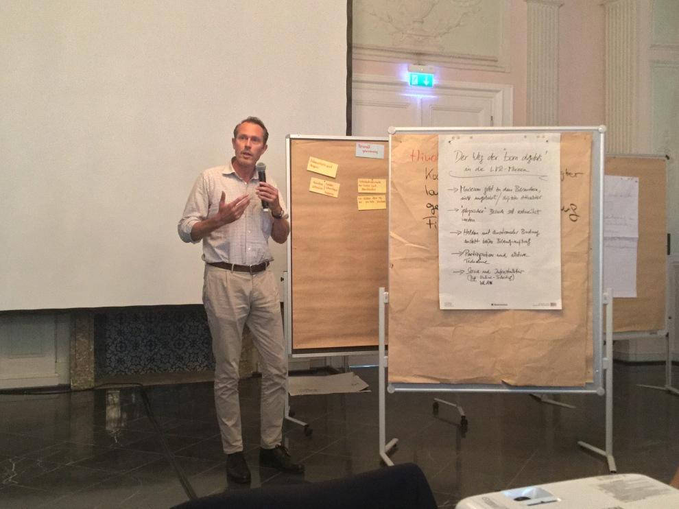 Das Bild zeigt die Vortragssituation mit Herrn Dr. Thomas Otten, Direktor des MIQUA, neben Präsentationswänden.