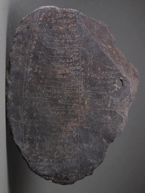 Die Tafel aus Schiefer ist mit hebräischen Buchstaben beschriftet. Aufgelistet sind Namen und Beträge.