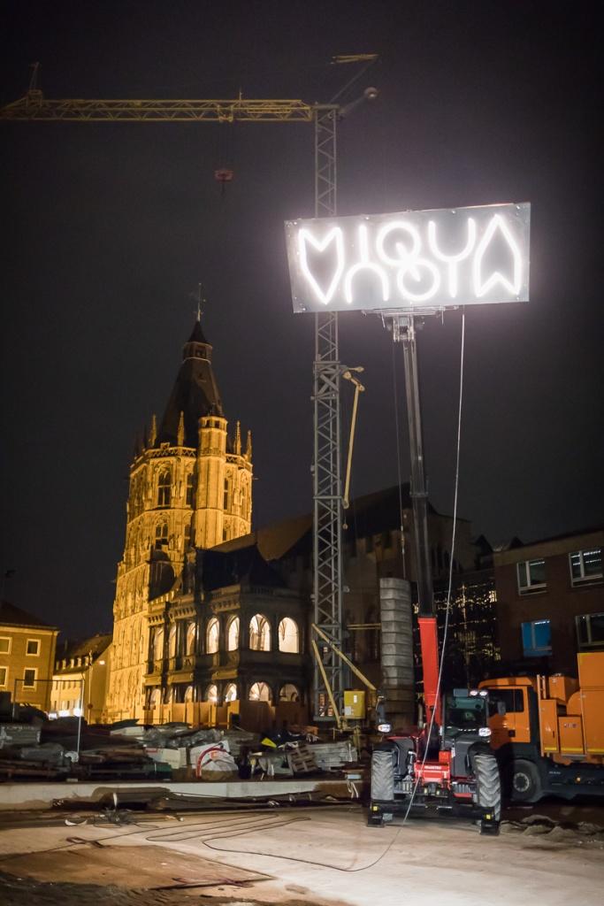 Das Logo des MiQua wurde mithilfe eines Krans nach oben gezogen und leuchtet über der Baustelle. Im Hintergrund sind die Renaissance-Laube und der Rathaus Turm zu sehen.