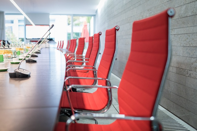 Leere rote Konferenzstühle an einem langen Tisch simulieren mögliche Räumlichkeiten einer Gesprächsrunde.