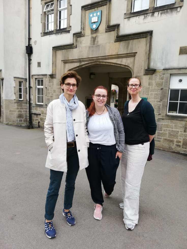 Die Mitarbeiterinnen des MiQua stehen in Leeds vor einem Gebäudeeingang. Christiane Twiehaus ganz links trägt einen beigen Kurzmantel und grauen Schal dazu. Malin Drees steht in der Mitte mit weißem T-Shirt, schwarzer Hose und kariertem Blazer darüber. Tanja Potthoff rechts im Bild trägt eine schwarze Bluse zu einer weißen Hose. Alle drei tragen Brille und aufgrund der bevorstehenden Rückreise gemütliche Sneaker.