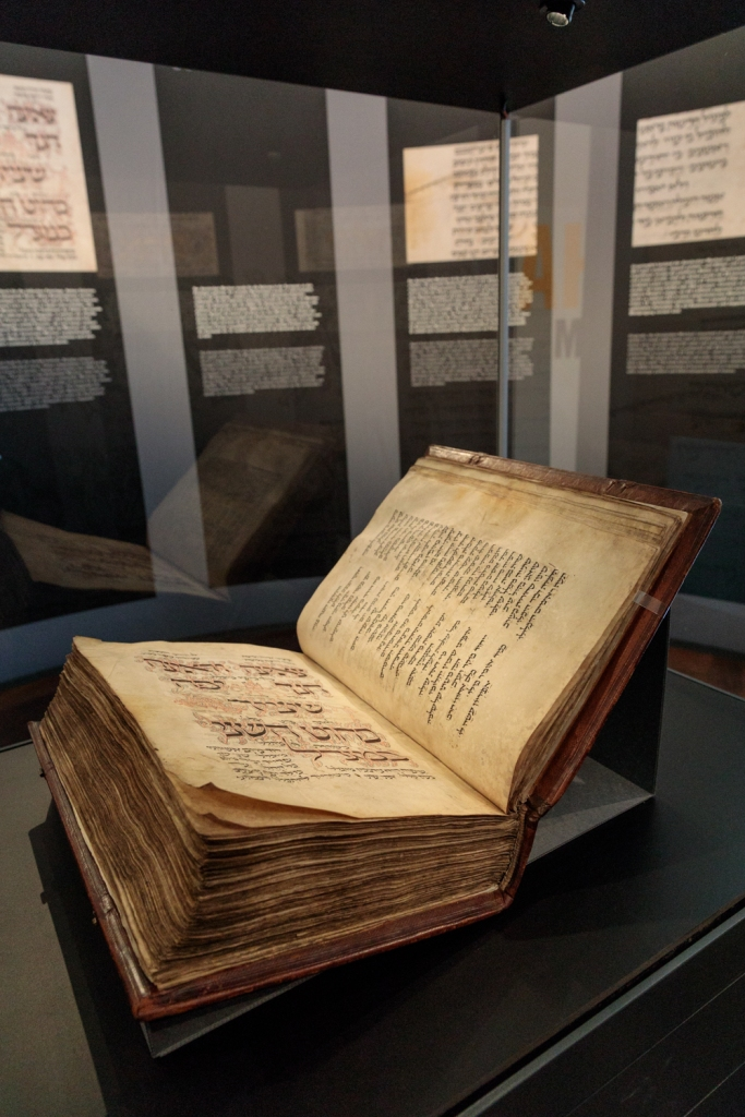 Der Amsterdam Machsor ist eine hebräische Handschrift aus dem Mittelalter. Das Foto zeigt das Manuskript aufgeschlagen in der Vitrine liegend. Im Hintergrund sind Teile der Ausstellungsarchitektur erkennbar.