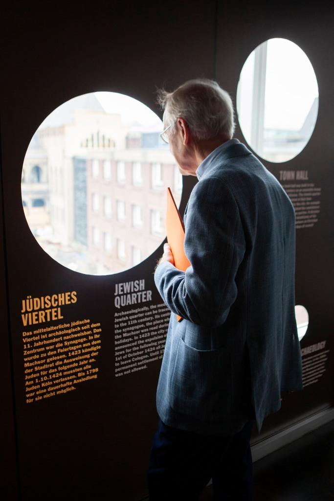 Ein Mann blickt durch Gucklöcher des beklebten Fensters auf die Baustelle des MiQua und damit auf das Gelände des mittelalterlichen jüdischen Viertels.