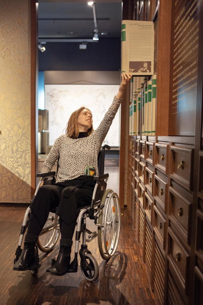 Eine MiQua Kollegin versucht, im Rollstuhl sitzend, interaktive Elemente in der Ausstellung zu nutzen. Dabei muss sie sich ganz hochrecken und seitlich an die Bücherwand mit ausziehbaren Elementen heranfahren.