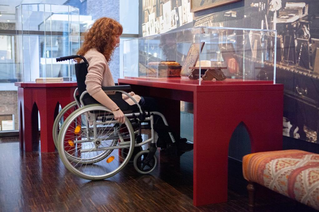 Eine Kollegin unterfährt mit dem Rollstuhl eine Vitrine. Sie kann die Exponate nur aus der Nähe sehen, weil der Sockel der Vitrine nicht geschlossen ist.