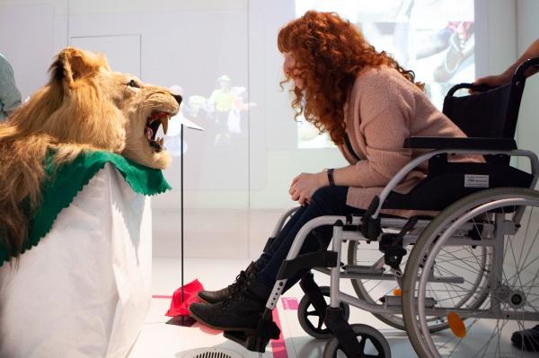Mitarbeiter*innen des MiQua durften die Ausstellung im Rautenstrauch-Joest-Museum mit Erlaubnis des Museumsdienstes Köln erfahren. Eine Kollegin steht im Rollstuhl sitzend einem Löwenkopf als Exponat gegenüber und blickt ihm ganz tief in die Augen.
